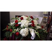 Funeral sympathy half casket with red and white flowers.